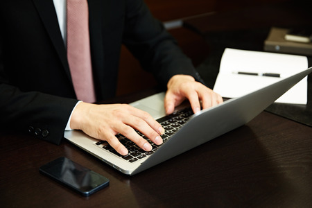 working on computer: Businessman working with laptop computer Stock Photo