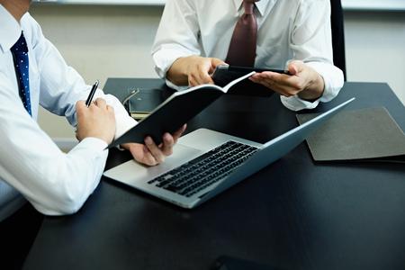 Twee jonge ondernemers met behulp van laptop op vergadering