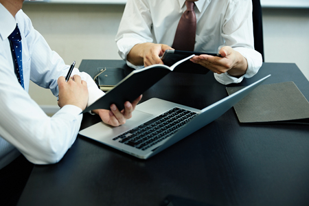 Two young businessmen using laptop at meeting