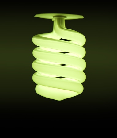 Energy-saving lamp on dark green background Stock Photo