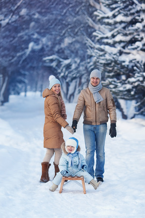 Portrait of Young family and his baby in a winter park Stock Photo