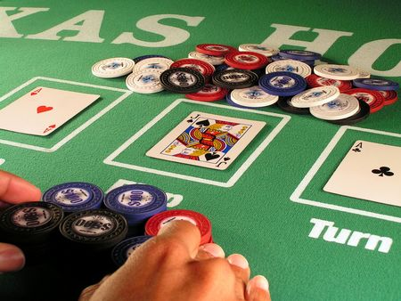a poker player betting all of his chips in a hand of no limit texas holdem. Stock Photo