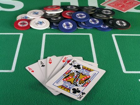 hold em: Full house in a hand of poker with chips on a green felt table. Stock Photo