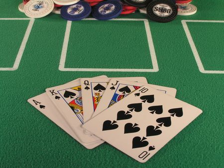 jack pot: royal flush of spades in a poker hand on a green felt table top.