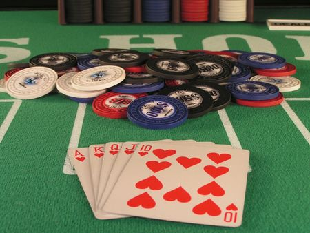 royal flush of hearts in a poker hand on a green felt table top. photo