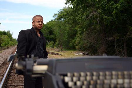 Jonge man met zijn schrijfmachine op de trein sporen. Stockfoto