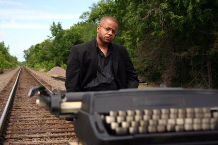 Jonge man met zijn schrijfmachine op de trein tracks.