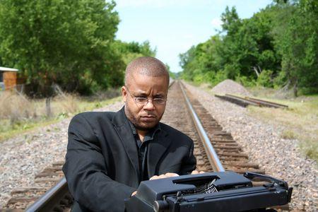 Jonge man met zijn type machine op de trein sporen.