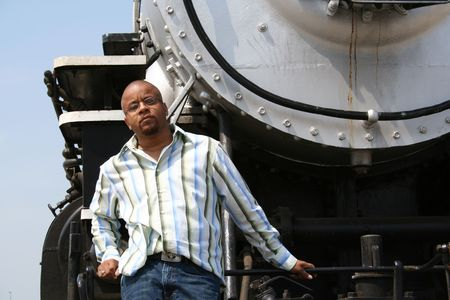 Young man posing on old train locomotive Stock Photo