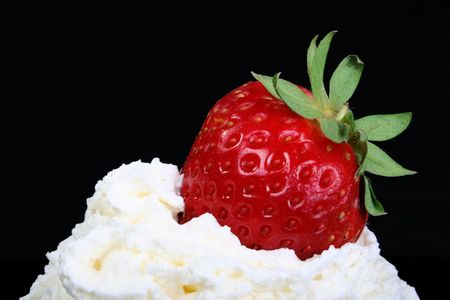Fresh strawberry placed on whipped cream with black background