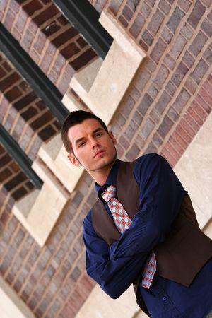 Young man posing in front of building with shirt and tie photo