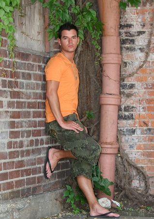 flops: Young man posing on a brick wall in orange shirt Stock Photo