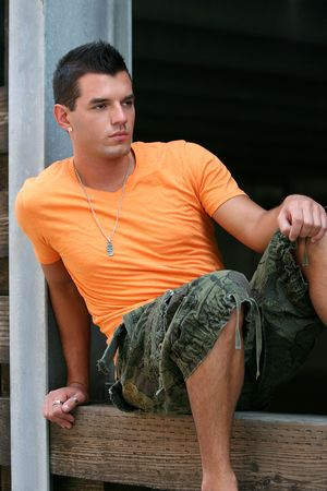flops: Young man posing in orange shirt with rings