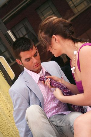 Young lady fixing a young mans necktie photo