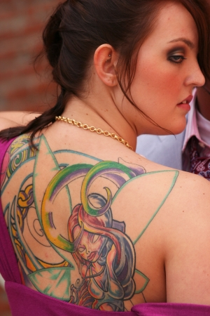 Lady looking over shoulder with fairy tattoo on back photo