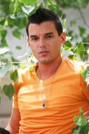 Young man posing in orange shirt with necklace photo