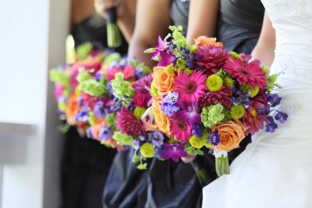 Bruid en bruidsmeisjes houden hun bloemen Stockfoto