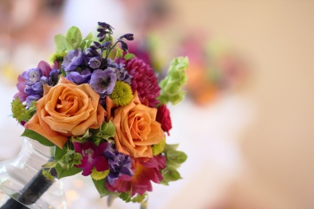 One of the bridesmaids floral boquets in vase on table