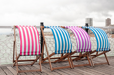 windy city: Colorful sunbeds at the seaside Stock Photo