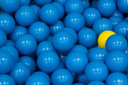 plastic balls, yellow plastic ball among blue plastic ball, concept : different, hiding power, fear, beware, spy