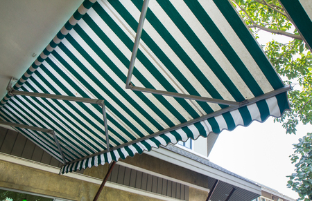 green and white stripe awning of shop, low angle photo
