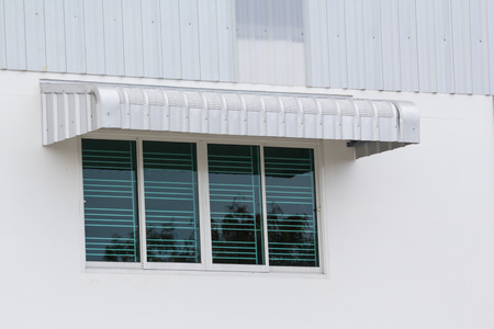 silver metal awning over window of factory, steel awning