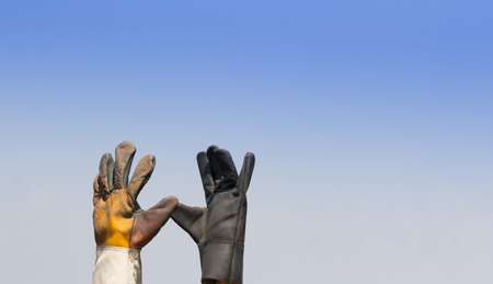 leather safety glove against blue sky, concept : give me five on site