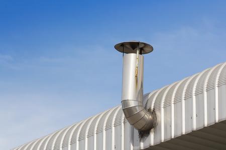steel smoke stack on aluminium factory roof Stock Photo