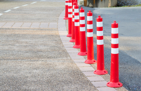Orange plastic bollards with traffic reflective on footpath