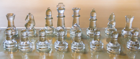 transparent chess set on wooden table Stock Photo