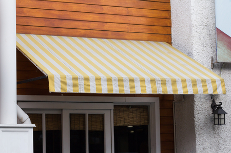 yellow and white striped awning over entrance at shop
