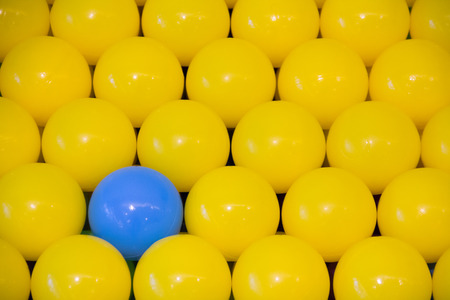 blue plastic ball among yellows balls, business different concept