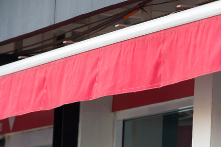 red awning over windows of store