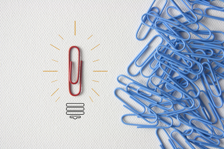 group direction: Individuality symbol and independent thinker concept and new leadership concept or individuality as a group of paperclip on canvas with one individual in the opposite direction as a business icon.