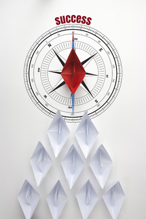 Leadership and success with a business team as red paper boat on compass in the shape of an arrow and the leader as a red manager at the top directing the people to succeed in the business world.