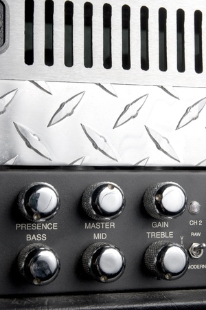 black and metallic guitar apmlifier panel with metallic shiny knobs for bass treble and middle control photo