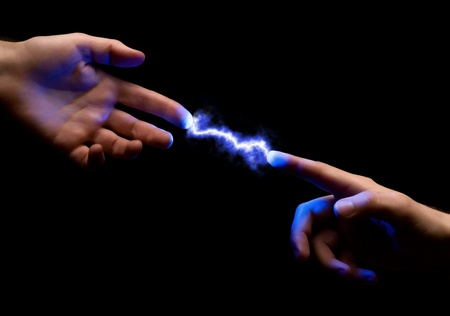 two fingers: blue powerful electric spark between two fingers of mans hands on black background Stock Photo
