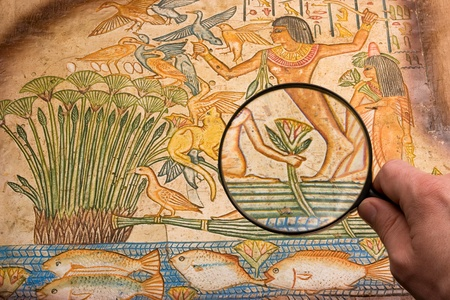 hand with big magnifying glass on old antique egyptian papyrus discovering Stock Photo - 8720152