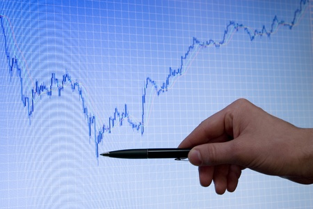 forex: blue forex stock chart on computer monitor is growing, hand with pen is pointed on lower peak of graph Stock Photo