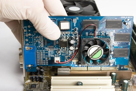 expert in white mitten on hand is installing video card into motherboard by plugging it into AGP socket Stock Photo - 9258002