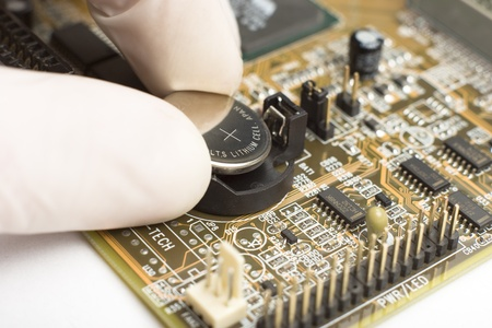 Experte für weiße Handschuh auf der Seite setzt Runde reflektierende Batterie mit Pluszeichen in Computer-motherboard