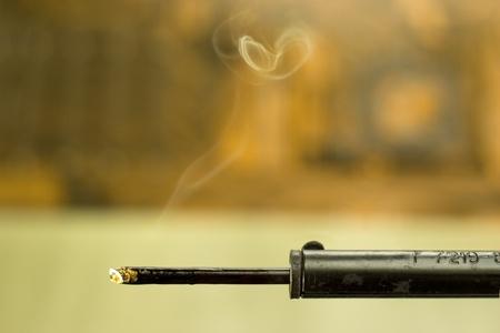 Closeup geheizte Lötkolben mit Rauch auf verschwommenen Hintergrund