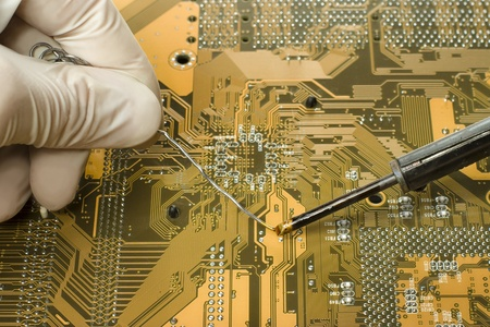 solder: close up view of expert in white mitten is repairing circuit board using soldering iron and solder Stock Photo