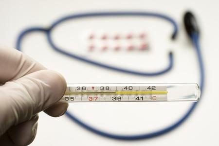 Doctor hält Thermometer mit hohen Temperaturen mit Stethoskop und Tabletten auf Hintergrund