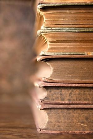 Stack antikes bejahrt Bücher über Holztisch und Hintergrund mit interessanten Textur auf butts
