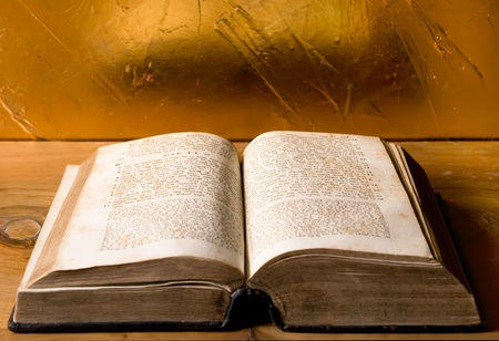 bible reading: opened antique jewish bible lies on wooden table in front of golden wall Stock Photo