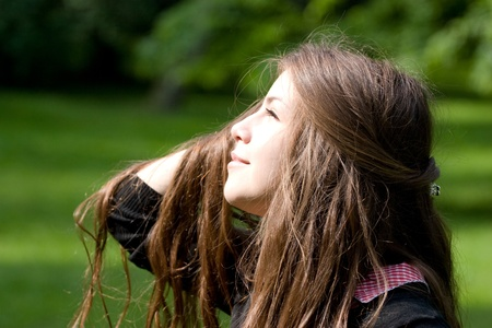 beautiful girl in park is looking at the sun with luxurious hair