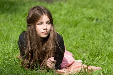 attractive girl is lying on the grass in the park, starring to the infinity and thinking