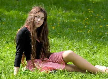 attraktives Mädchen mit langen braunen Haaren im Park sitzen auf dem Rasen