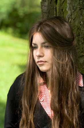 portrait of attractive girl in the park is thinking or dreaming